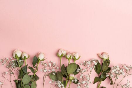 Border of little rose and gypsophila on a pink background. Place for text. Flat lay, top view. 写真素材