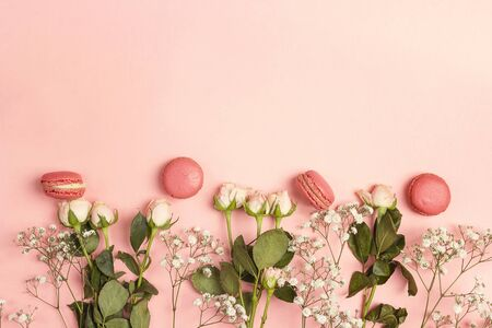 Border of small  white flowers and roses with macarons on pink background. Place for text. Flat lay, top view. 写真素材