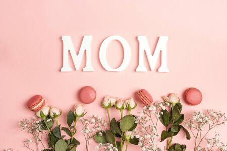 Small white flowers and roses with macarons and word Mon on pink background. Mother day concept. 写真素材