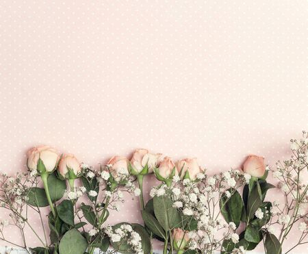 Border of little rose and gypsophila on a pink polka dot background. Place for text. Flat lay, top view.