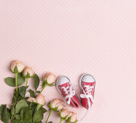 Pink baby girl sneakers with little rose flowers on a pink background. Copy space, flat lay, top view.