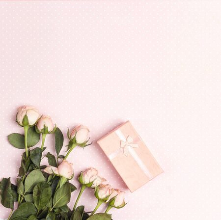 Small roses and gift box on a pink polka dot background. Place for text. Flat lay, top view.