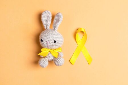 Childhood Cancer Awareness Golden Ribbon with toy bunny on yellow background. Childhood Cancer Day February, 15.