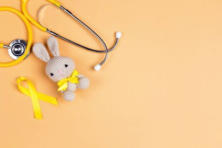 Childrens toy with a Childhood Cancer Awareness Golden Ribbon and stethoscope on yellow background with copy space. Childhood Cancer Day February, 15.