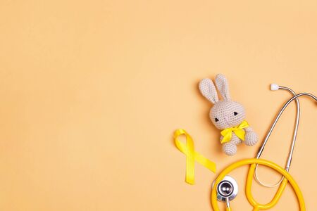 Childhood Cancer Awareness Golden Ribbon with toy bunny and stethoscope on yellow background with copy space. Childhood Cancer Day February, 15.