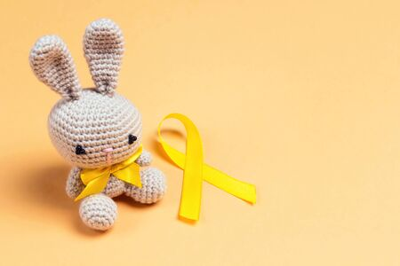 Childrens toy with a Childhood Cancer Awareness Golden Ribbon on yellow background with copy space. Childhood Cancer Day February, 15.