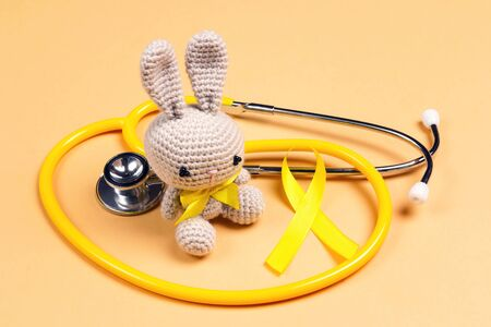 Childrens toy with a Childhood Cancer Awareness Golden Ribbon and stethoscope on yellow background. Childhood Cancer Day February, 15.