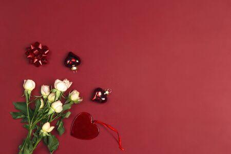 Red background with a bouquet of small roses and a hearts. Place for text, top down composition. St. Valentines Day concept. Stock Photo