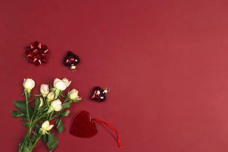 Rode achtergrond met een boeket van kleine rozen en een hart. Plaats voor tekst, compositie van bovenaf. St. Valentijnsdag concept. Stockfoto