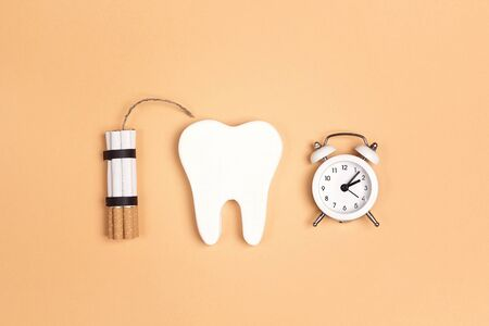Tooth with cigarettes dynamite and alarm clock on yellow background. Smoking and dental health problem. Stop smoking, World No Tobacco Day. Standard-Bild