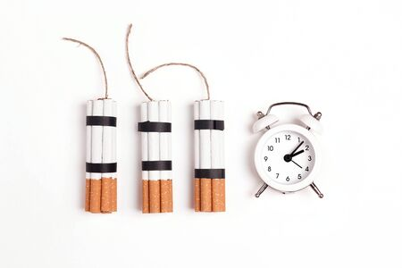 Dynamite made from cigarettes with alarm clock on white background. Stop smoking concept. Flat lay, top view with copy space.