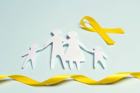 Paper family silhouette with yellow awareness ribbon on a blue background. Suicide prevention and Childhood Cancer Awareness concept. Banco de Imagens