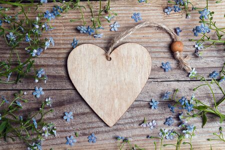 Decorative heart with place for text surrounded by forget-me-not flowers on an old wooden table.