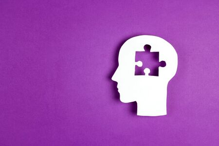 Human head paper silhouette with a puzzle piece cut out on the purple background. Mental health symbol. Alzheimers and dementia, mental illness and brain disorder.