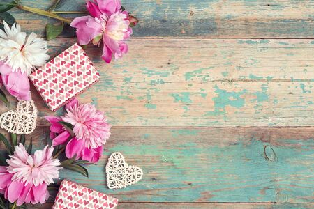 Festive background with pink peonies, gifts and hearts on an old turquoise table with shabby paint. Place for text, top down composition. Reklamní fotografie