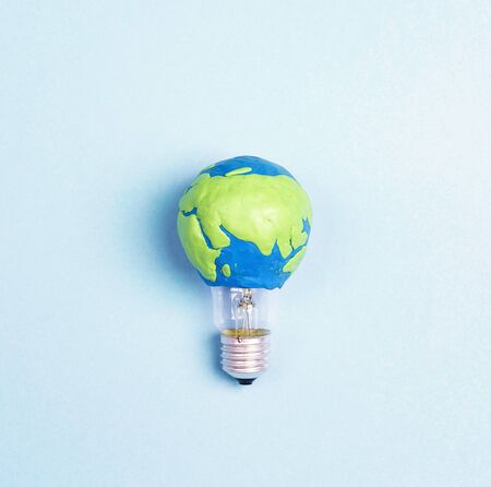 Light bulb with plasticine Earth planet model on blue background. Global ecology, International Day of Energy Saving or Earth Hour concept.
