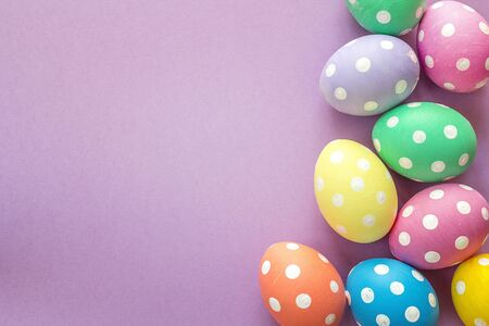 Colored Easter eggs on urple background. Space for text.Top view. Archivio Fotografico