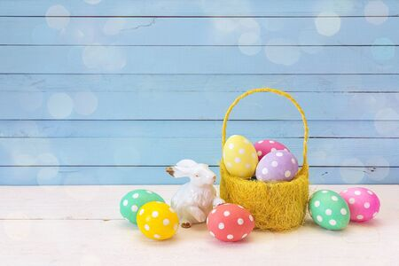 Yellow basket with Easter eggs and a rabbit on a blue background. Place for the text. Banque d'images