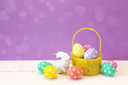 Yellow basket with Easter eggs and a rabbit on a purple background. Place for the text. Easter decoration. Banque d'images