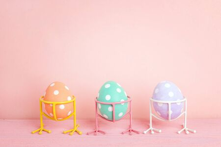 Funny Easter eggs on bird legs on pink background. Copy space. Banque d'images