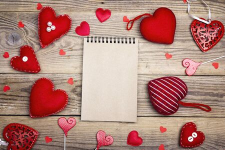 Open blank notebook with Valentine hearts on old wooden background. Copy space. Valentines day background. Top view.