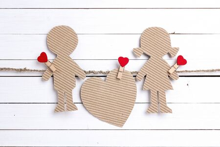 Cardboard silhouettes girl and boy with heart on white wooden background. Space for text. Valentine's Day background.