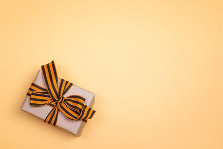 Gift box with st george ribbons on the yellow background. Defender of the Fatherland Day, Victory Day concept. Space for text.
