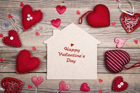 Greeting Valentines Day card with home symbol and red hearts on wooden background. Happy Valentine's Day.