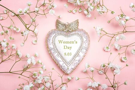 Women's Day greeting message on decorative heart with gypsophila flowers on pink background. International Womens Day, March 8.