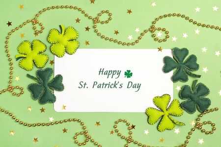 St.Patrick's day greeting card with felt clover leaves and golden beads on green background.