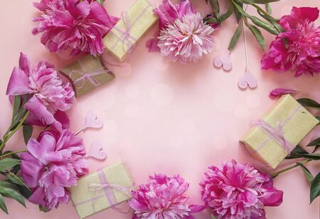 Romantic background with peonies, gift boxes and hearts on pink. Copy space. Top view.