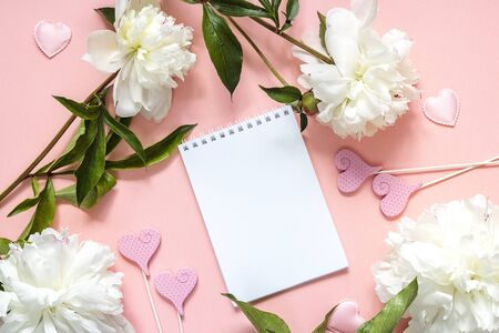Blank open notepad with white peonies on a pink background. Place for a message, top view. Romantic background.
