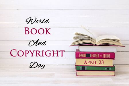 World book and copyright day, april 23. Poster with stack of books and open book on wooden table.