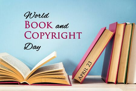 World book and copyright day, april 23. Poster with stack of books with open book on against a blue background.