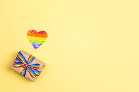 Gift box with rainbow LGBT ribbon and heart on a yellow background. Homosexual and lgbt concept.