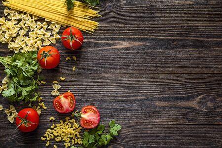 Tło z makaronem, pomidorami i ziołami na ciemnym drewnianym stole z miejsca kopiowania. Miejsce na tekst. Widok z góry.