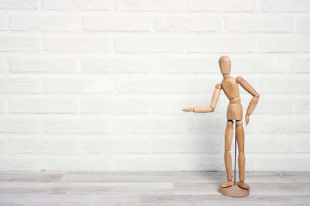 Wooden dummy in a proposing pose on the background of a white brick wall. Space to insert text or design.