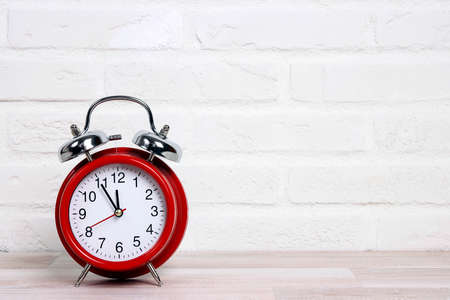 Classic red alarm clock against the white brick wall. Copy space for text.
