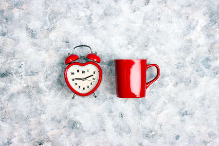 Red classic alarm clock and red coffee mug on gray canvas background. Wakeup or break time concept.