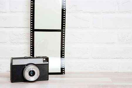 Old retro camera with camera film agianst white brick wall. Space for text or image.