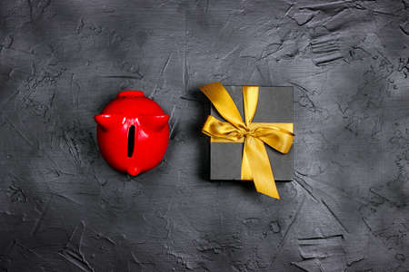 Black gift box with gold ribbon and piggy bank on a black background. Holiday or black friday concept. Top view with copy space. Stock Photo