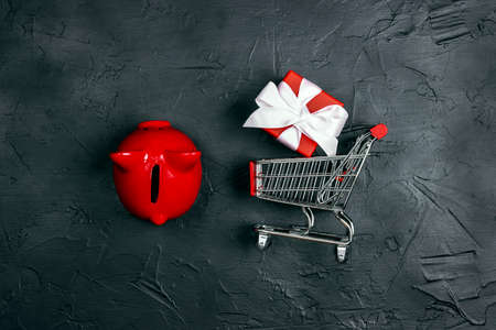 Shopping trolley with red gift box and piggy bank on a black background. Holiday or black friday concept. Top view with copy space.