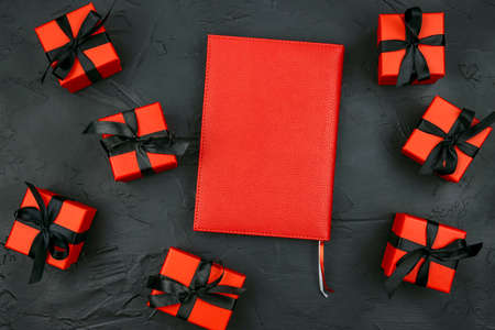 Red notebook with red gift boxes with black ribbons on a black background. Holiday or black friday concept. Top view with copy space.
