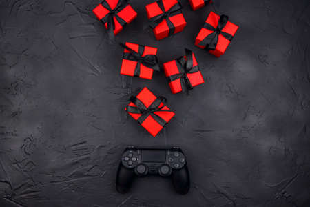 Joystick gaming controller with red gift boxes on black background. Holiday sale or black friday concept. Top view with copy space.