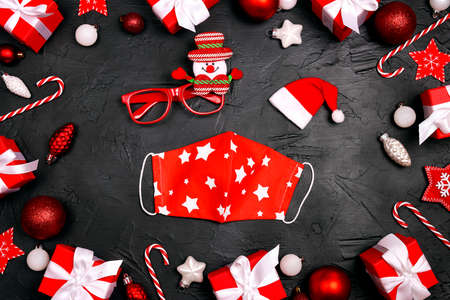 Set of funny glasses and medical mask on a black background with red Christmas decorations. Safe Christmas celebration during the coronavirus. Flat lay design. 스톡 콘텐츠