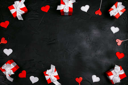 Frame of red gifts and hearts on black background. Valentine's day concept. Copy space, top view.