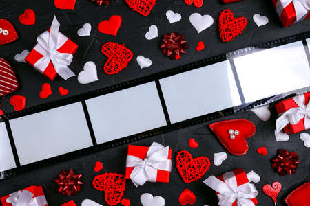 Film form frame with hearts and gifts on black background. Space for text or image. Top view Valentine's day composition. Stockfoto