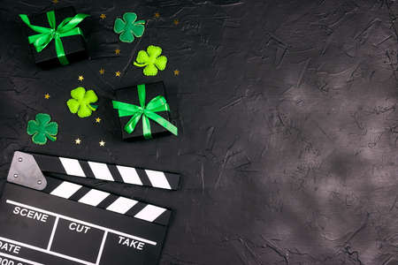 Movie clapper board with decorative clover leaves, gift boxes and gold stars on black background with copy space. Saint Patrick's Day movies concept. Фото со стока