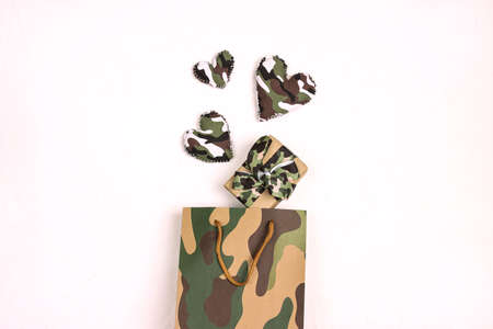 Khaki shopping bag with gift box and camouflage hearts on white background. Defender of the Fatherland Day, February 23. Space for text. Reklamní fotografie