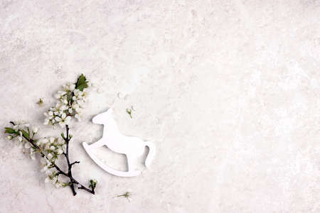 Mini rocking horse toy with apple blossom branches on a light marble background. Copy space. Top view.